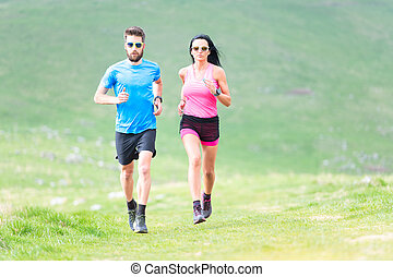 Action of runners in hilly meadows in the summer. Man and woman