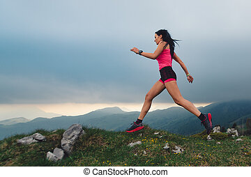 Action of sporty woman with athletic body during a nature race