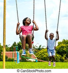 African kids having fun swinging in park. - Action portrait...