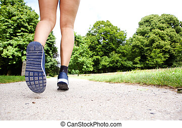 Action portrait of lady runner shoes on path