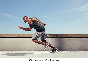 Action shot of a sporty young man running outdoors