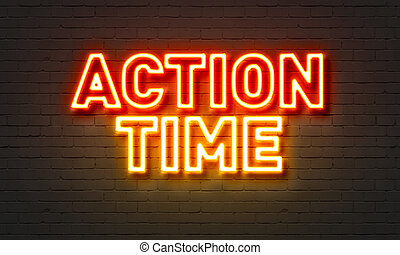 Action time neon sign on brick wall background.