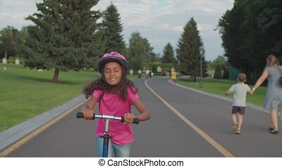 Active african little girl riding scooter in park - Active ...