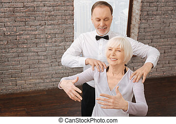 Active aged couple performing in interaction in the dance studio