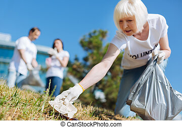 Active aged lady picking up litter in the park