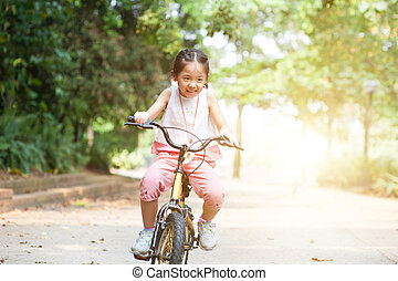 Active Asian child riding bicycle outdoor.