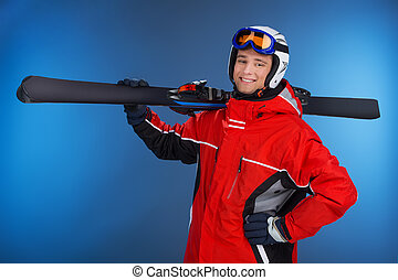 Active attractive guy walking with ski in hands. Looking and smiling at camera isolated over blue background