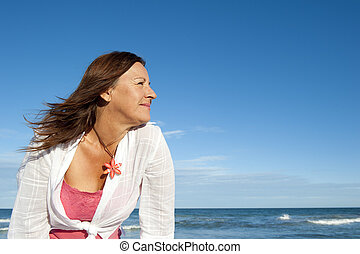 Active attractive senior woman ocean background