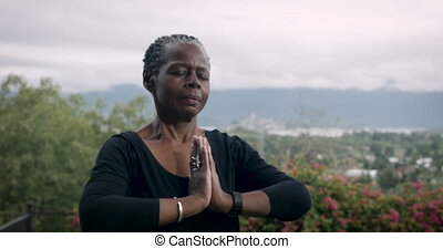 Active baby boomer African American woman exercising yoga...