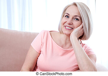Active beautiful middle-aged woman smiling friendly and looking into the camera. Woman's face close up.