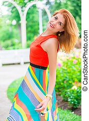 active beautiful woman in a bright dress posing