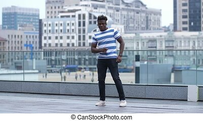 Active black male dancing afrobeat style in city - Active...