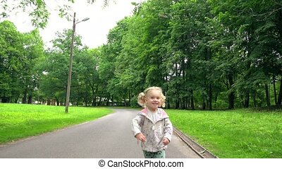 Active blond girl with pigtails running through park road in...