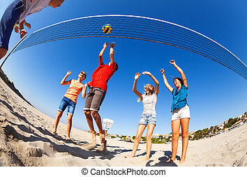 Active boys and girls playing volleyball on beach