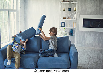 Active boys having fun while sitting on the sofa and fighting