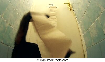 Active cat playing with toilet paper and unrolling it in lavatory.