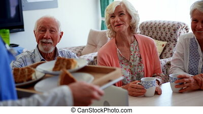 Active Caucasian senior people smiling on dining table at ...