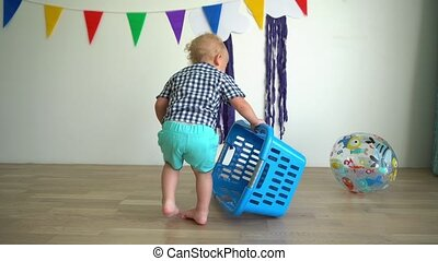 Active child boy fall off laundry box and play with ball....