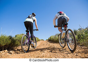 Active couple cycling uphill on a bike ride in the country ...