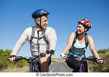 Active couple going for a bike ride in the countryside on a ...