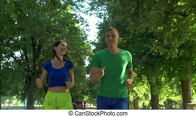 Active couple jogging together in summer park