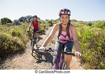 Active couple on a bike ride in the countryside on a sunny ...