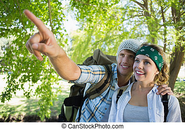 Active couple on a hike with man pointing