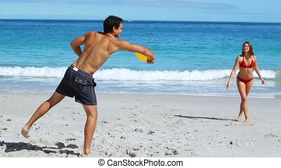 Active couple playing frisbee on the beach