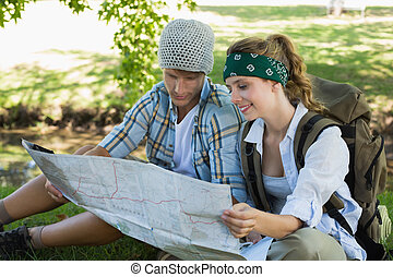 Active couple sitting down on a hike reading map