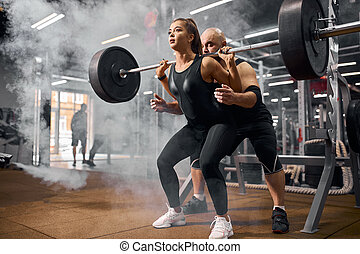 Active couple training in gym hall