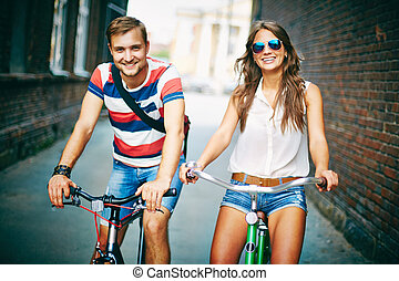 Active dates - Portrait of happy young couple on bicycles on...