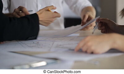 Active discussion of charts and plans on paper with your hands and pencils behind a desk.