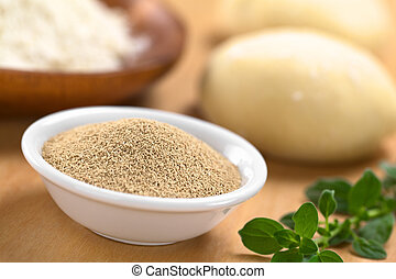 Active dry yeast in small bowl with fresh oregano on the side, flour and dough in the back (Selective Focus, Focus in the middle of the dry yeast)