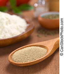 Basic ingredients of a pizza: Active dry yeast on wooden spoon with oregano, flour, salt, pepper, tomato and basil in the back (Selective Focus, Focus in the middle of the dry yeast)