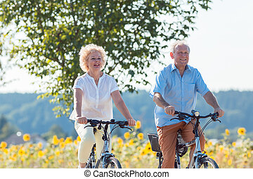 Active elderly couple riding bicycles together in the countrysid