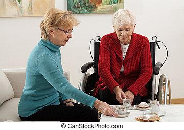 Active elderly - Two elder women drinking coffee and...