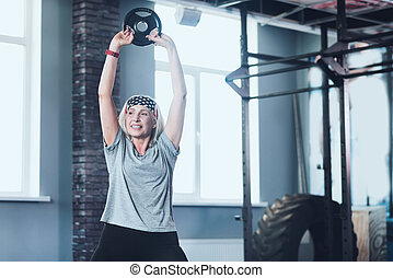 Active elderly woman lifting weight disk