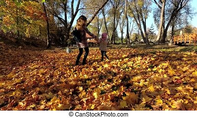 Active family play between autumn leaves in park. Mother...