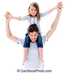 Active father giving his daughter a piggyback ride against a...