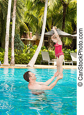 Active father teaching his toddler daughter to swim in pool ...
