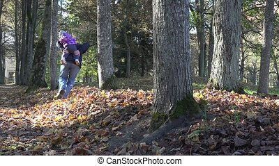 Active father with baby on shoulders run between autumn trees and leaves. 4K