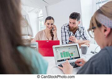 Active female entrepreneur talking on mobile at a shared desk in