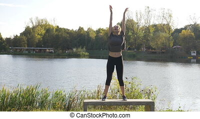 Active female model with curled hair doing yoga on a sunny day of summer in nature near the lake