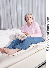 active female senior relaxing on couch