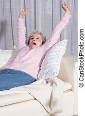 active female senior stretching on couch