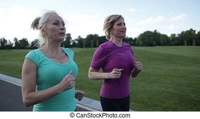 Active fit senior female athletes running outdoors -...