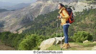 Active fit young woman hiker wearing a backpack pausing to...