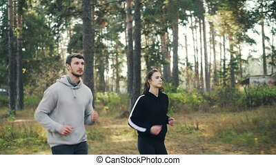 Active friends in sportswear are jogging in park on sunny...