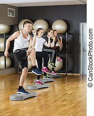 Active Friends Performing Step Exercise In Gymnasium
