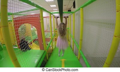 Active girl hang on handle and slide down at indoors playground